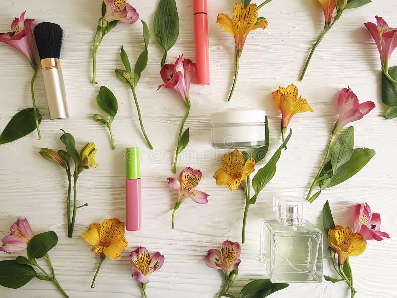 Florece el fondo de madera del alstroemeria, cosméticos decorativos del modelo poner crema imagenes de archivo