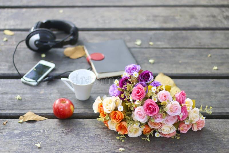 Florece el ramo, los libros y la taza en la tabla de madera fotografía de archivo libre de regalías