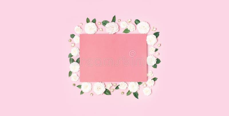Florece la composici?n Documento en blanco rosado, rosas frescas blancas y hojas verdes sobre fondo rosado apacible Endecha plana foto de archivo
