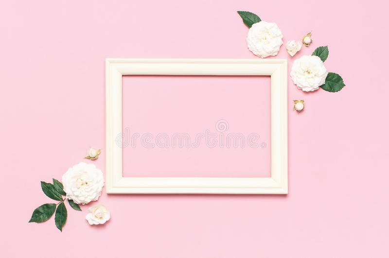 Florece la composici?n Marco blanco de madera de la foto, rosas frescas blancas y hojas verdes en fondo rosado apacible Endecha p fotos de archivo