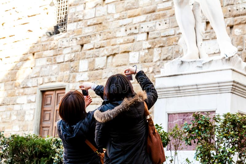 Florence, Italië - Maart 13, 2012: Jonge toeristen die beelden van het standbeeld nemen dichtbij Uffizi-Galerijen royalty-vrije stock foto's