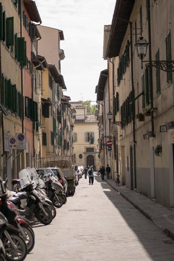 Florence Italien - 24 April, 2018: en gammal gata med parkerade cyklar och några personer arkivbild