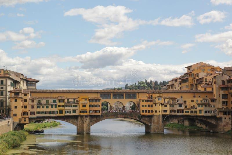 Florence Italien - September 03,2017: H?rlig sikt downriver till Ponte Vecchio den gamla bruden i den bl?a himlen och molnet arkivbild