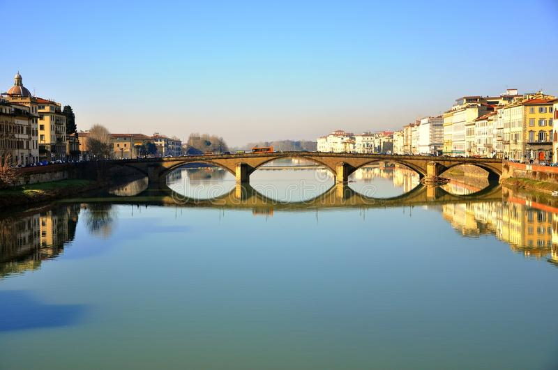 Beautiful bridge over Arno river in Florence city , Italy. Buildings and bridges mirror in the river Arno in Florence, Italy. Urban cityscape stock photo
