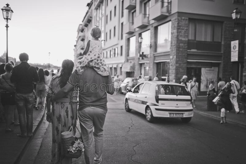 Florence, Italy-July 20, 2014. A married couple with a child on the shoulders of father go through the city. Black and white photo royalty free stock photography