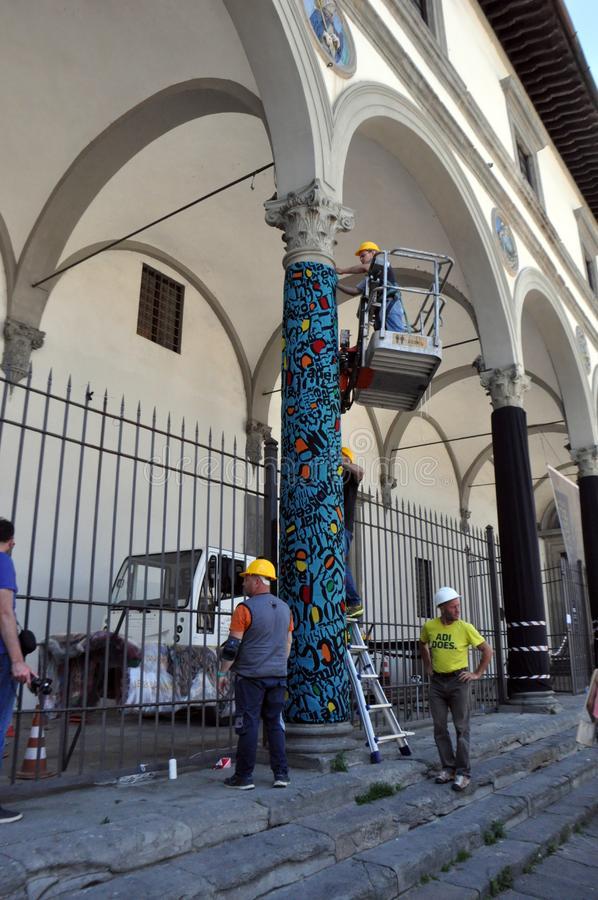 FLORENCE, ITALY - JUNE 12, 2016: Italian workers decorate the column tiles, mosaics, cloth. stock image