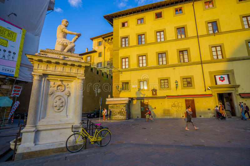 FLORENCE, ITALY - JUNE 12, 2015: Statue in the middle of the square, shadow reflected in a big yellow old building stock photos