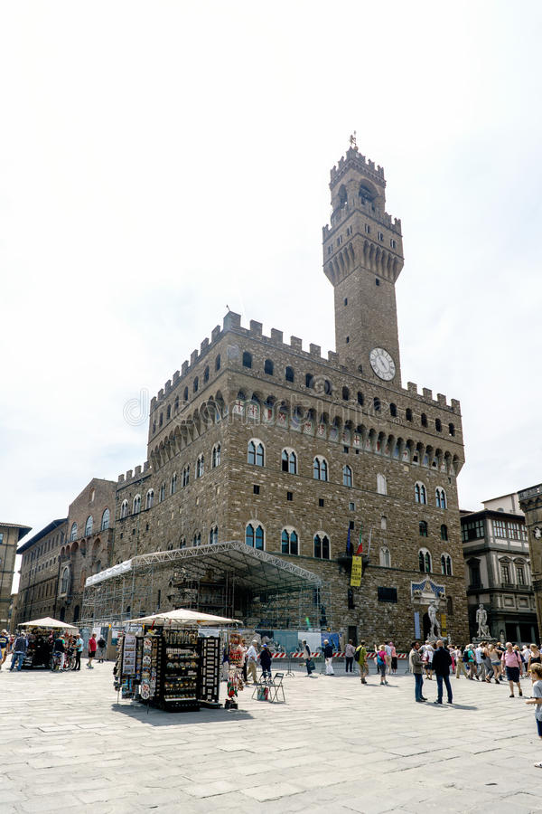View of the fortified palace called `Palazo Vecchio` located in the square `Piazza della Signoria` with people walking, next stock photography