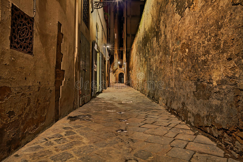 Florence, Tuscany, Italy: narrow alley at night. Florence, Tuscany, Italy: dark narrow alley in the old town at night lit by old street lamps royalty free stock photo