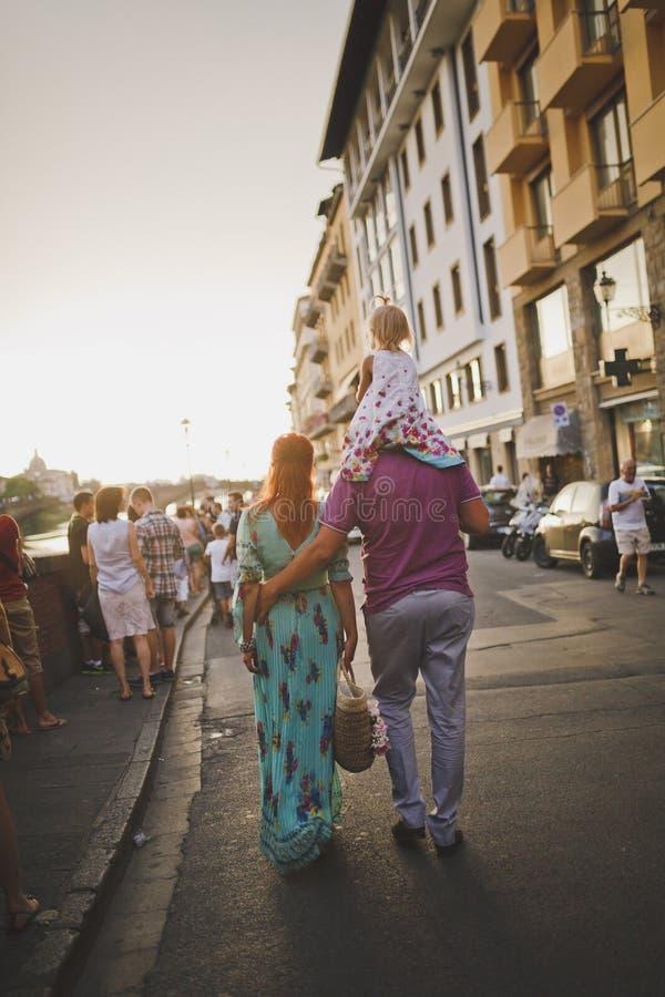 Florencia, Italia 20 de julio de 2014 Una pareja casada con un niño en los hombros del padre pasa a través de la ciudad fotografía de archivo libre de regalías