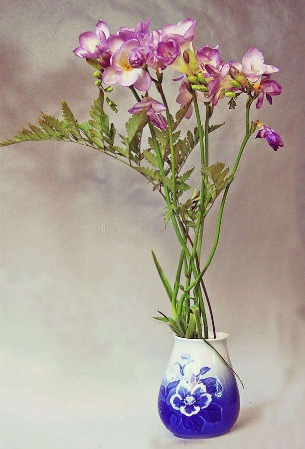 Florero azul con las flores foto de archivo