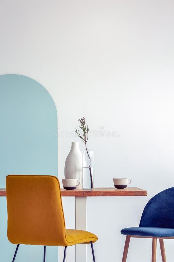 Florero blanco en la tabla de madera con el comedor de lujo interior con la pared blanca y azul imagenes de archivo