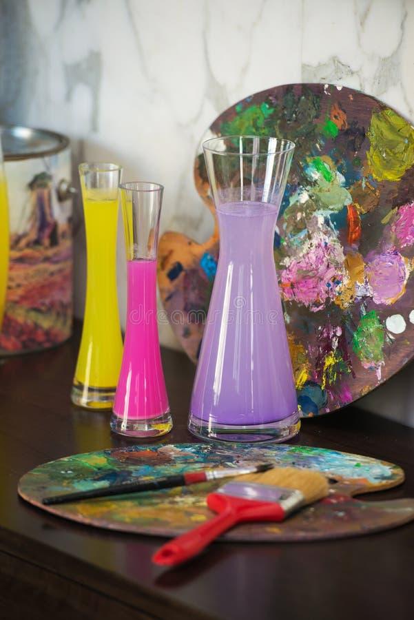Florero con agua coloreada palette Humor creativo Atmósfera artística foto de archivo