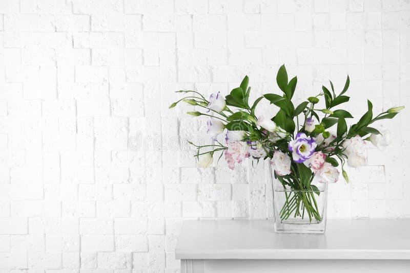 Florero con el ramo de flores hermosas en la tabla cerca de la pared de ladrillo imagen de archivo