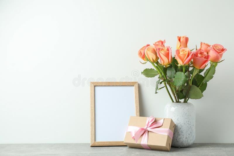 Florero con las rosas, el regalo y el marco vacío en la tabla gris contra el fondo blanco imágenes de archivo libres de regalías