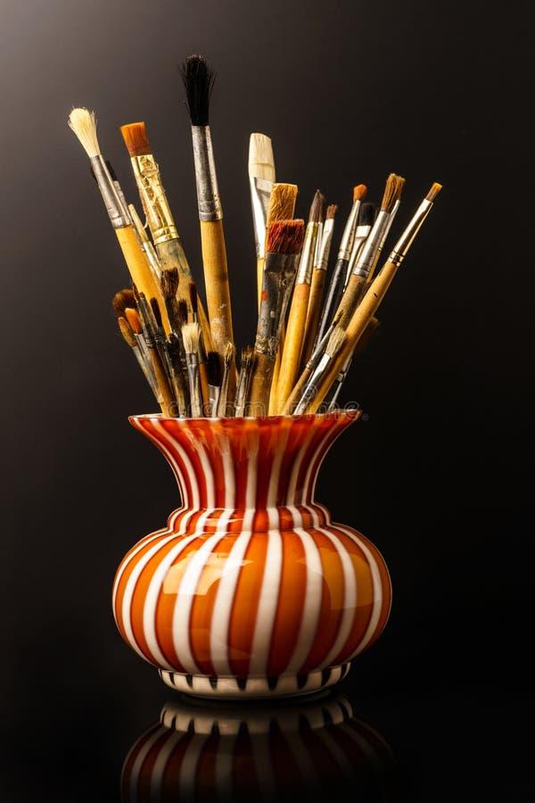 Florero con los cepillos artísticos en el fondo negro imágenes de archivo libres de regalías