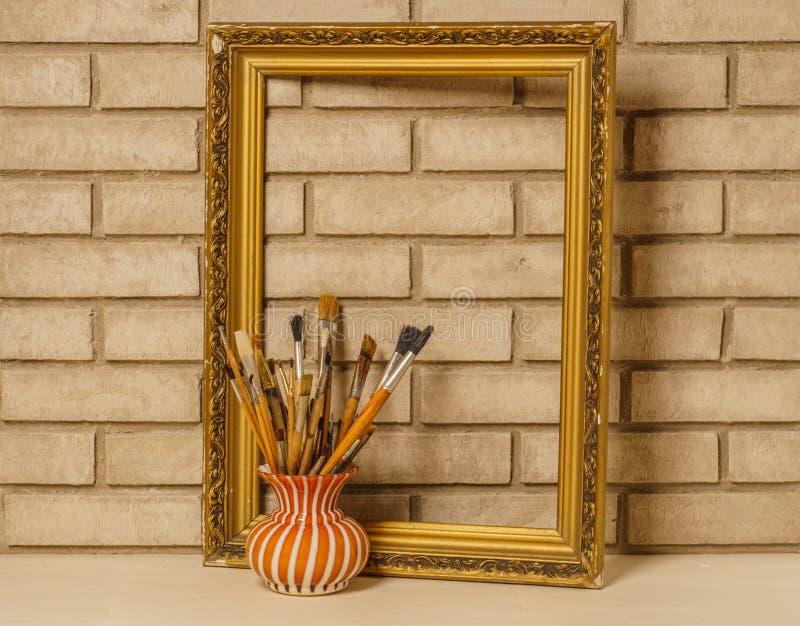Florero con los cepillos artísticos y el marco en el fondo del ol fotos de archivo