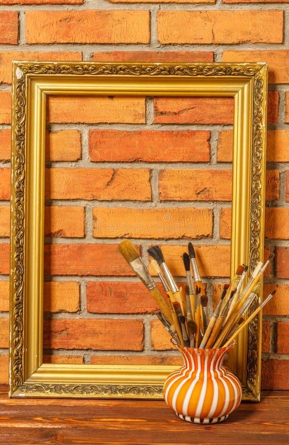 Florero con los cepillos artísticos y el marco en el fondo del ol fotografía de archivo