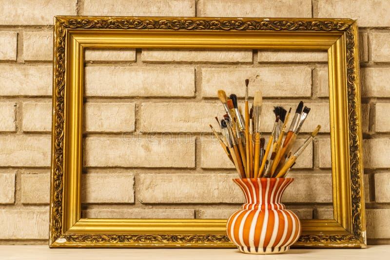Florero con los cepillos artísticos y el marco en el fondo del ol foto de archivo