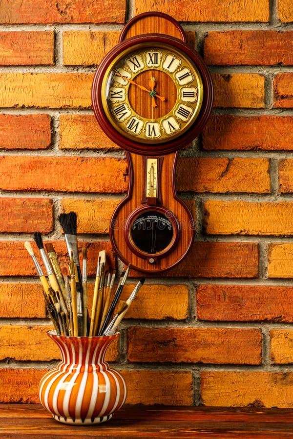 Florero con los cepillos artísticos y reloj de pared de madera viejo con el barome foto de archivo