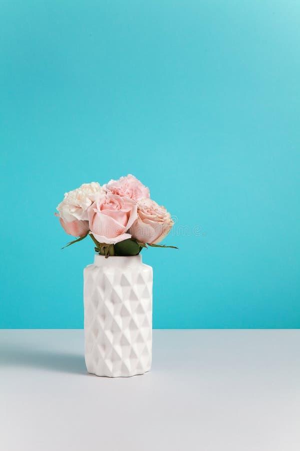 Florero de cer?mica blanco moderno con las rosas rosadas en soporte azul del fondo en yable gris composici?n minimalistic con el  fotos de archivo libres de regalías
