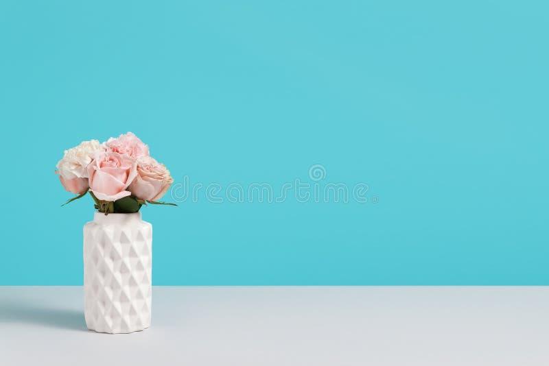 Florero de cer?mica blanco moderno con las rosas rosadas en soporte azul del fondo en yable gris composici?n minimalistic con el  imagen de archivo libre de regalías