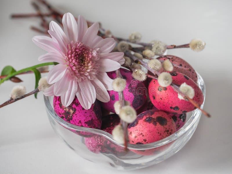 Florero de cristal coloreado rosa con el crisantemo rosado y huevos coloreados fotografía de archivo