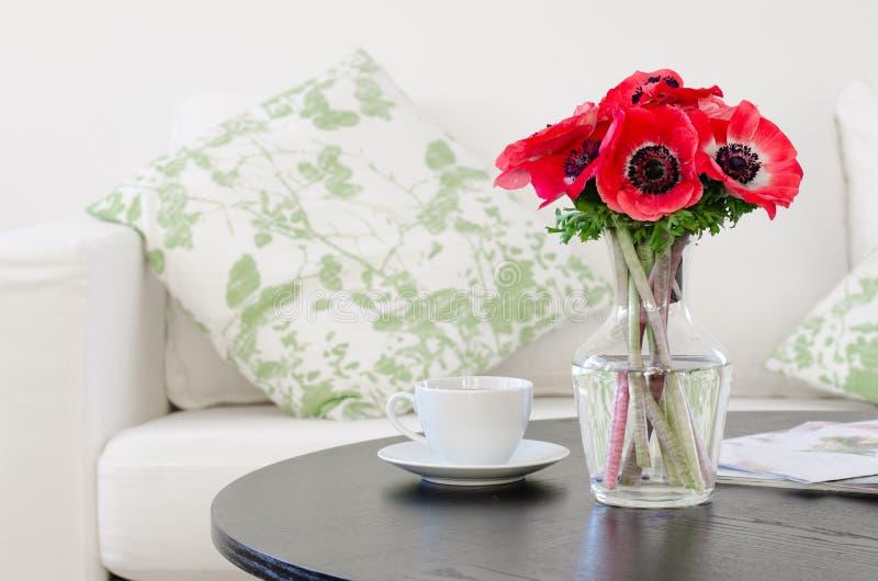 Florero de flores rojas en sala de estar blanca moderna imagen de archivo libre de regalías