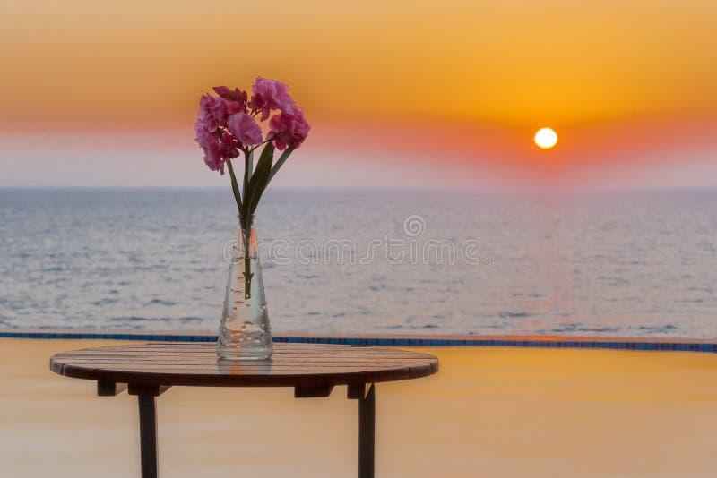 Florero en la tabla por el mar de desatención de la piscina en la puesta del sol foto de archivo libre de regalías