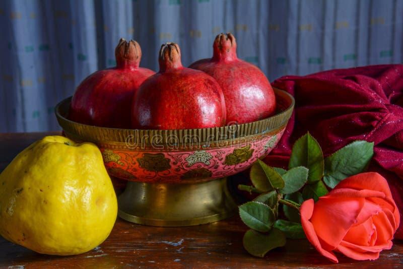 Florero indio viejo con la fruta y una rosa del escarlata imagen de archivo