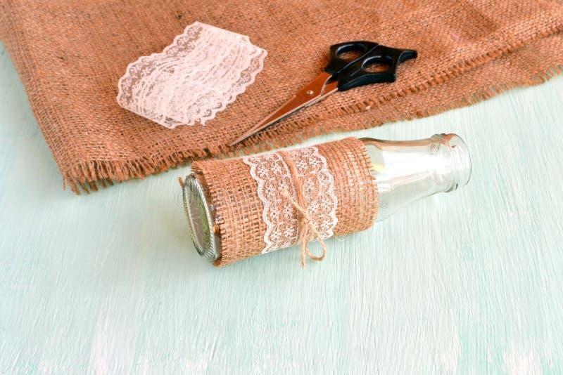Florero vacío hecho a mano, tijeras, arpillera, cordón Fije para el florero hecho a mano Cómo hacer el florero Material reciclado foto de archivo libre de regalías