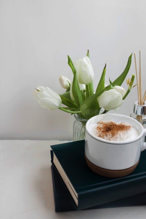 Florero y libros a lo largo de una taza de café imágenes de archivo libres de regalías