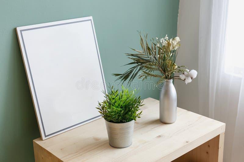 Florero y un cubo con las plantas verdes en una tabla cerca de una imagen con el espacio de la copia Lugar para el texto Interior imagen de archivo libre de regalías
