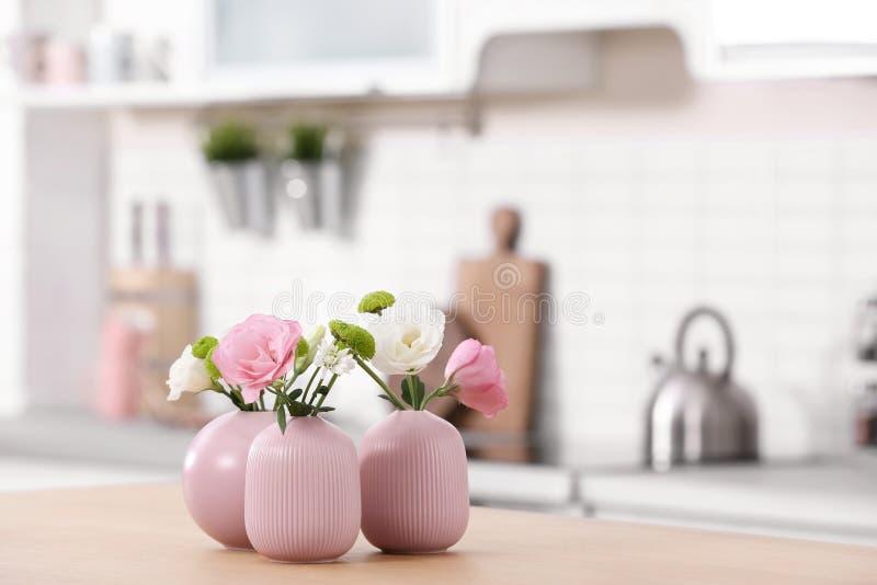 Floreros con las flores hermosas en la tabla en interior de la cocina fotografía de archivo