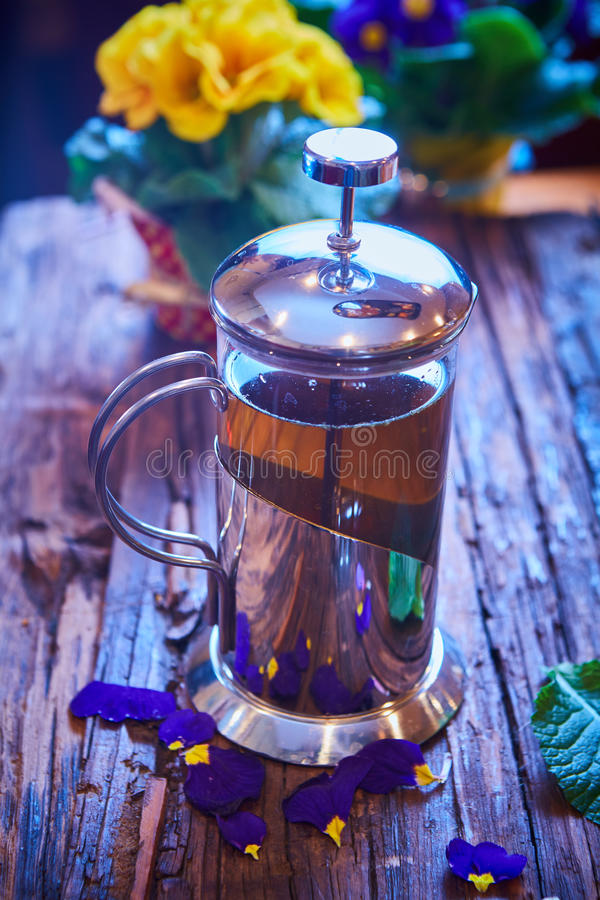 Floresça o chá no potenciômetro de vidro em uma tabela de madeira foto de stock royalty free