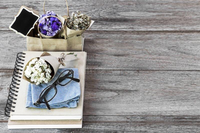 Floresça o ramalhete com caderno o copo e os vidros de café do latte sobre fotos de stock royalty free