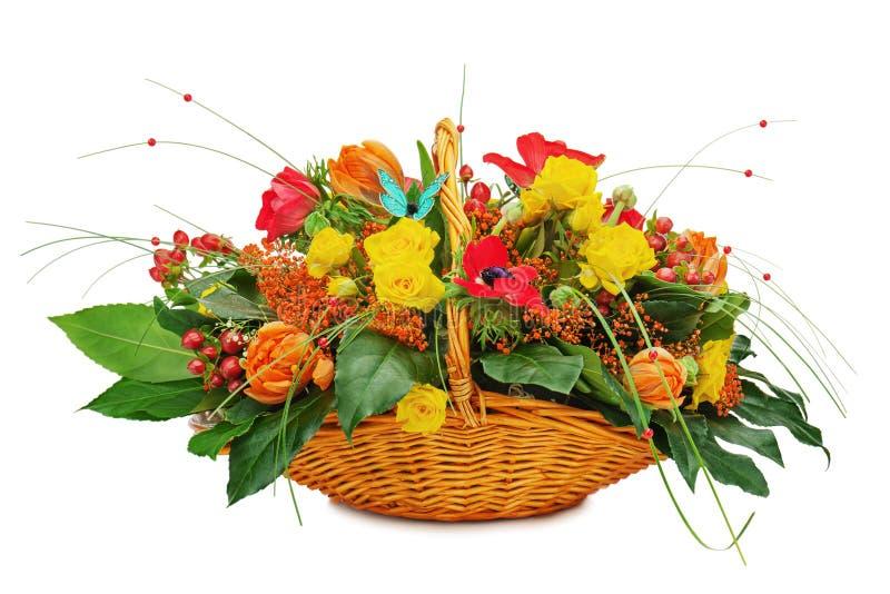 Floresça a peça central do arranjo do ramalhete em uma cesta de vime do presente foto de stock