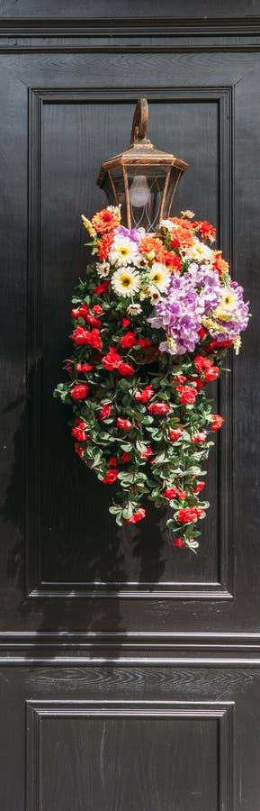 Flores adornadas en la lámpara con la pared de madera pintada negra en fondo imagenes de archivo