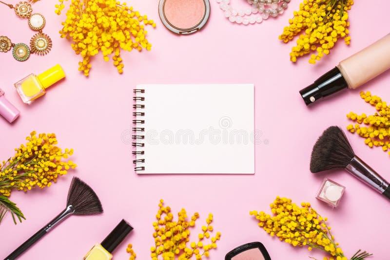 Flores amarelas da mola, notebok e alguns cosm?ticos no fundo cor-de-rosa da mola fotografia de stock royalty free