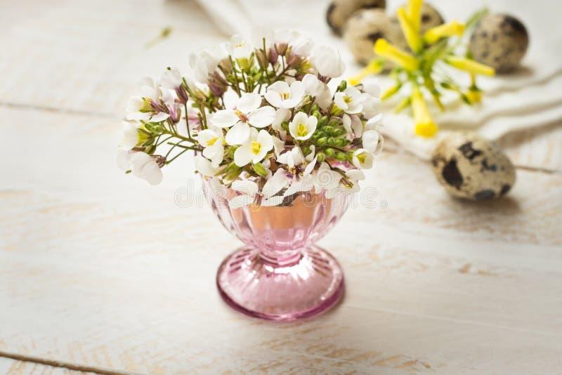 Flores amarillas blancas delicadas en la huevera cristalina, huevos de codornices, decoración de la primavera de Pascua imagenes de archivo