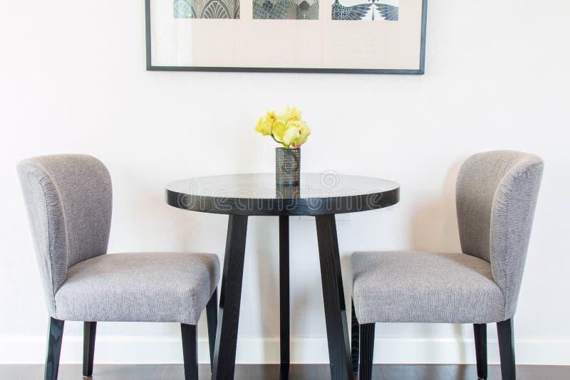 Flores amarillas en los floreros en la tabla y sillas por la pared imagen de archivo libre de regalías