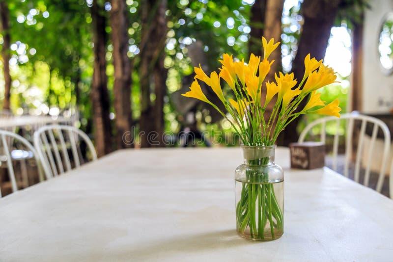 Flores amarillas en un florero de cristal en una tabla imagen de archivo