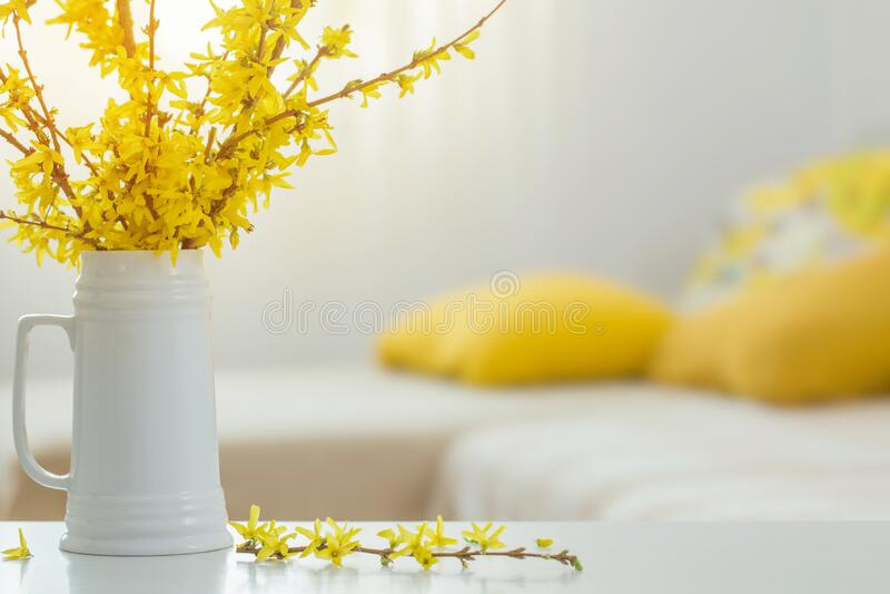 Flores amarillas primaverales en jarrón en interiores modernos imagen de archivo