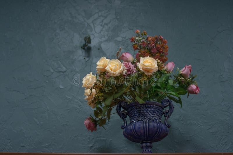 Flores artificiais bonitas e ? moda em um fundo azul fotografia de stock royalty free