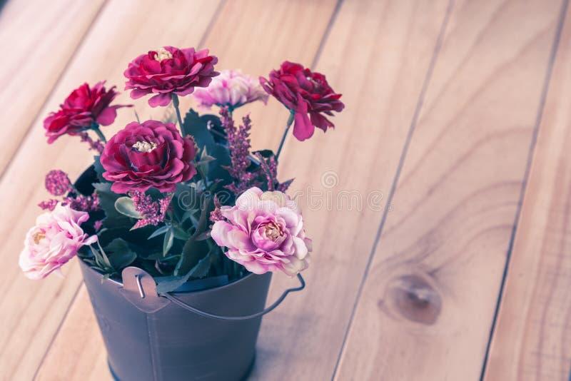 Flores artificiales coloridas en cubo en la tabla de madera fotografía de archivo