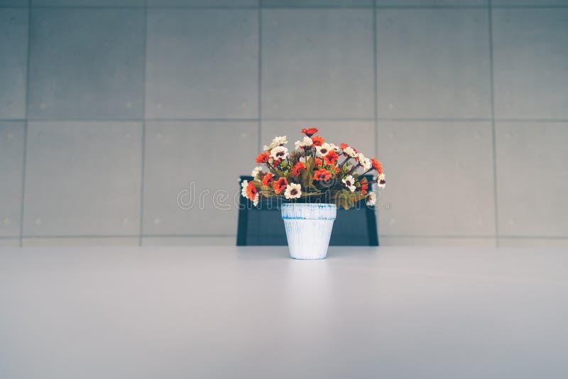 Flores artificiales coloridas en florero en la tabla con el fondo de la pared fotografía de archivo