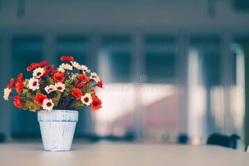 Flores artificiales coloridas en florero en la tabla con el fondo de la ventana de cristal fotos de archivo libres de regalías
