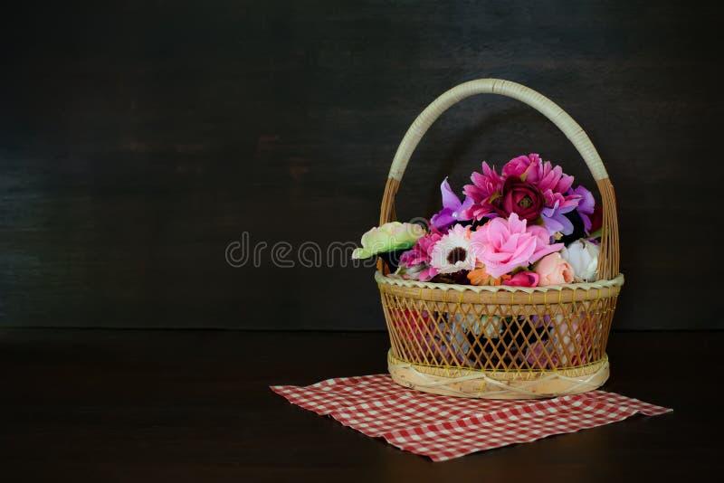 Flores artificiales coloridas hechas del paño en cesta en de madera imagen de archivo
