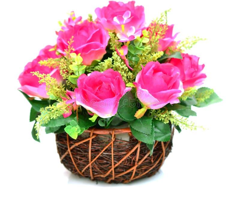 Flores artificiales en aislante de la cesta en blanco fotografía de archivo