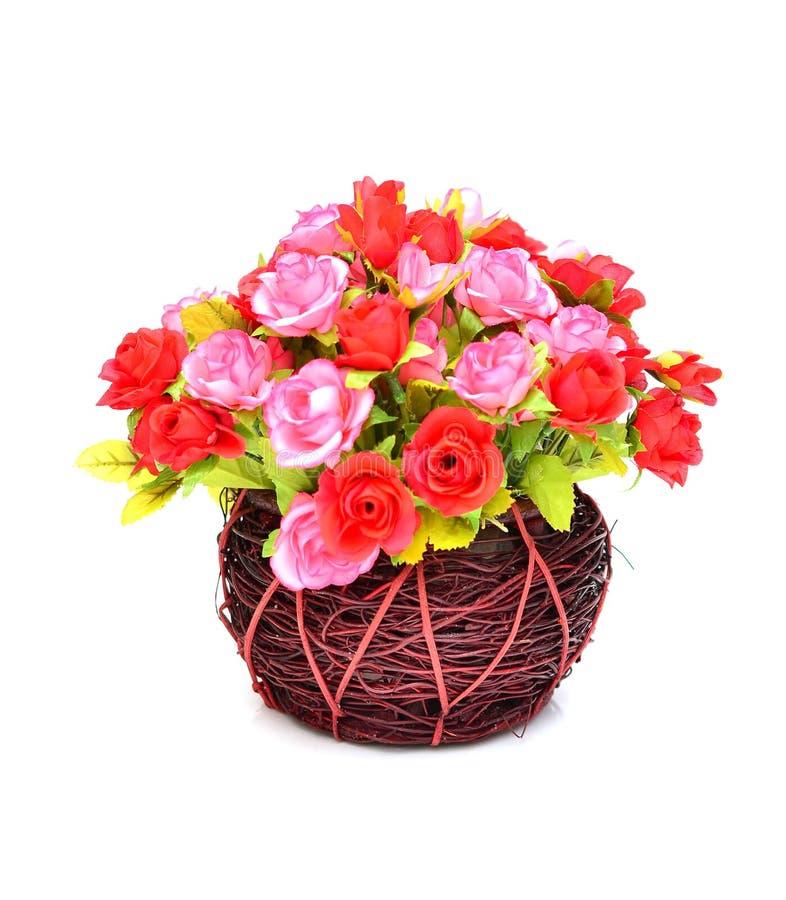 Flores artificiales en aislante de la cesta en blanco imagen de archivo